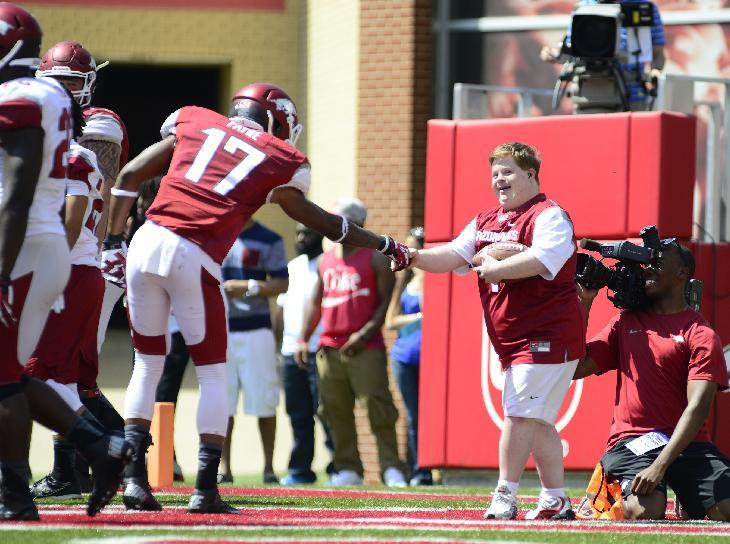 Arkansas Razorback fan Canaan Sandy is congratulated by Kendrick Payne (17) after scoring a touchdown on a play during their spring NCAA college football game, Saturday, April 26, 2014, in Fayetteville, Ark