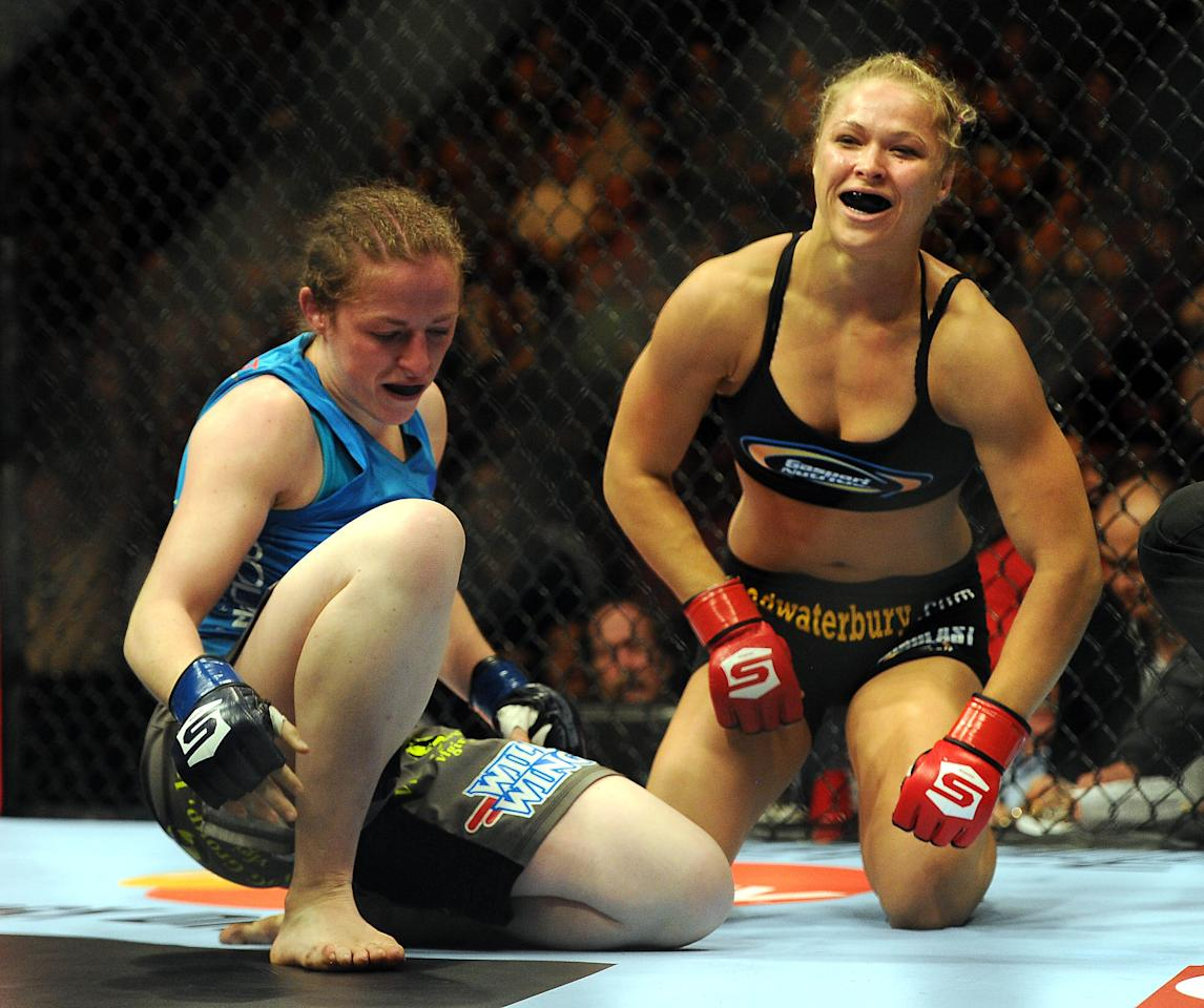 August 18, 2012; San Diego, CA, USA;   Ronda Rousey (black shirt) as she defeated Sarah Kaufman (blue shirt)during their Strikeforce MMA women's bantamweight title bout at the Valley View Casino Center. Rousey won in 54 seconds of the first round. Mandatory Credit: Jayne Kamin-Oncea-USA TODAY Sports