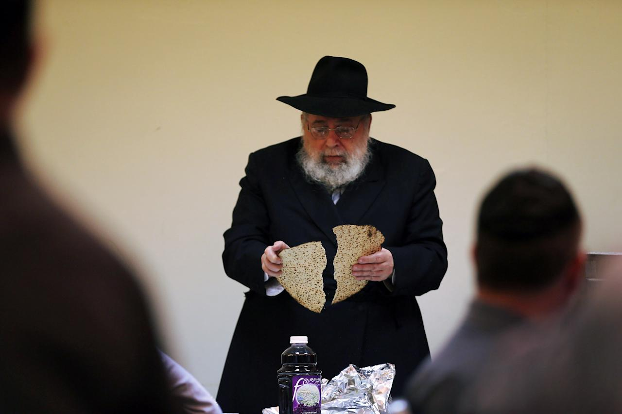 MIAMI BEACH, FL - MARCH 25:  Rabbi Efraim Katz breaks a piece of matzo as he leads a community Passover Seder at Beth Israel synagogue  on March 25, 2013 in Miami Beach, Florida. The community Passover Seder that served around 150 people has been held for the past 30 years and is welcome to anyone in the community that wants to commemorate the emancipation of the Israelites from slavery in ancient Egypt.  (Photo by Joe Raedle/Getty Images)