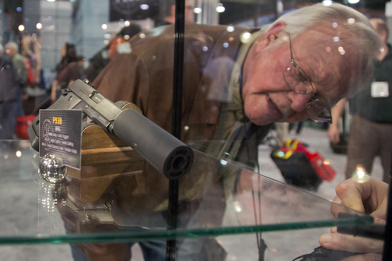A convention attendee looks through a Sig Sauer display case of various guns including a P938 Nightmare 9mm semiautomatic pistol.