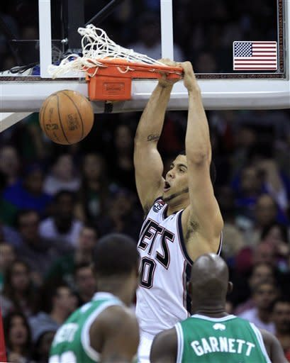 New Jersey Nets' Jordan Williams, top, dunks the ball during the second quarter of an NBA basketball game against the Boston Celtics in Newark, N.J., Saturday, April 14, 2012. (AP Photo/Mel Evans)
