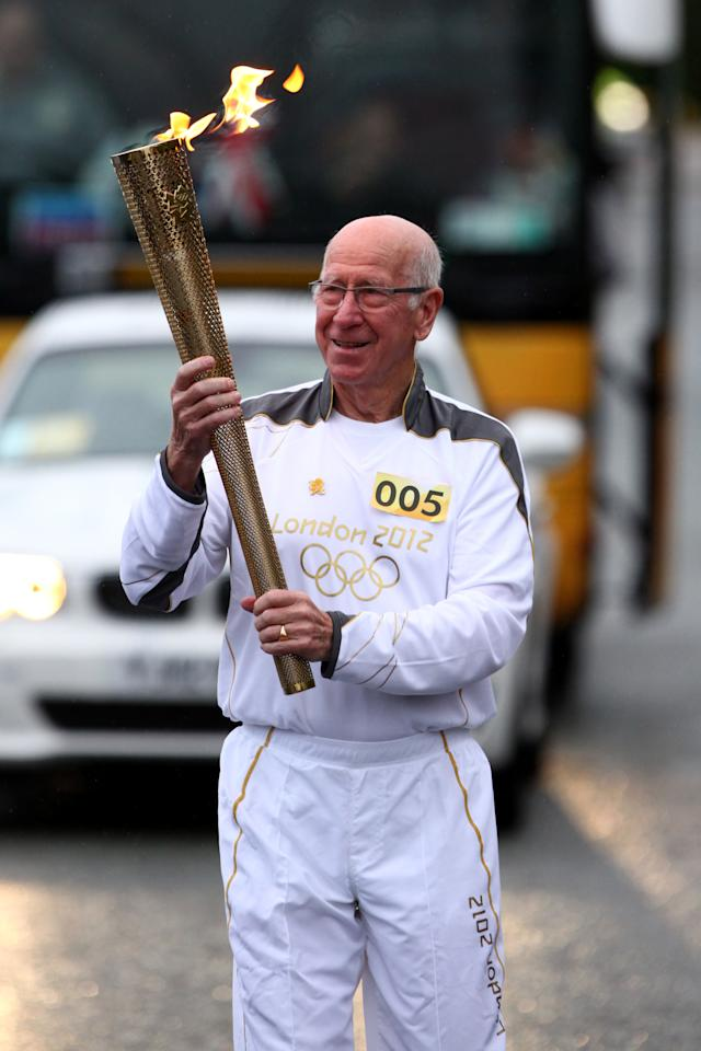 MANCHESTER, UNITED KINGDOM - JUNE 24:  In this handout image provided by LOCOG, Torchbearer 005 Sir Bobby Charlton carries the Olympic Flame on the Torch Relay leg between Salford and Moss Side on Day 37 of the London 2012 Olympic Torch Relay on June 24, 2012 in Manchester, England. The Olympic Flame is now on day 37 of a 70-day relay involving 8,000 torchbearers covering 8,000 miles.  (Photo by LOCOG via Getty Images)