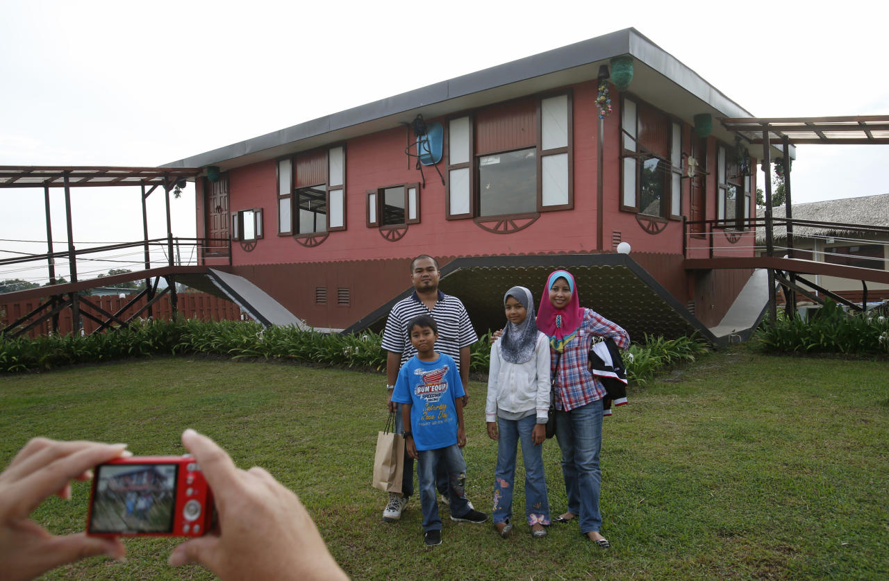 Tourists pose with an upside-down house in Tamparuli in Malaysia's state of Sabah on Borneo island September 17, 2012. Built for tourist attraction, the traditional Sabah village house was built with everyday households items like computer, refrigerator, sofa sets, dining table and beds - but all items are upside down. REUTERS/Bazuki Muhammad (MALAYSIA - Tags: SOCIETY TRAVEL) - RTR3832O