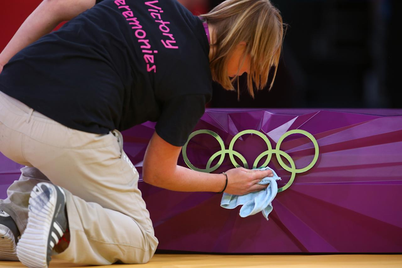 A volunteer polishes the rings on the medal stand at the judo on Day two of the London 2012 Olympic Games at ExCeL on July 29, 2012 in London, Englan  (Photo by Michael Steele/Getty Images)