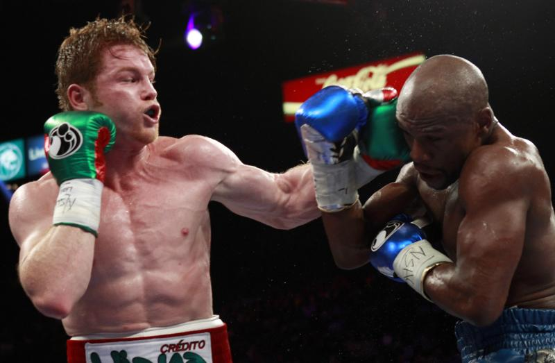 WBC/WBA 154-pound champion Canelo Alvarez (L) punches at Floyd Mayweather Jr. of the U.S. at the MGM Grand Garden Arena in Las Vegas, Nevada, September 14, 2013. REUTERS/Steve Marcus (UNITED STATES - Tags: SPORT BOXING)