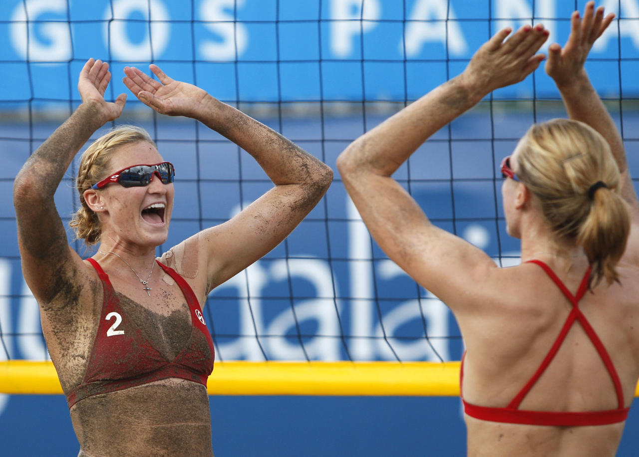 U.S.' Heather Hughes, left, celebrates with teammate Emily Day after defeating Chile in a women's beach volleyball match at the Pan American Games in Puerto Vallarta, Mexico, Sunday Oct. 16, 2011. (AP Photo/Ariana Cubillos)