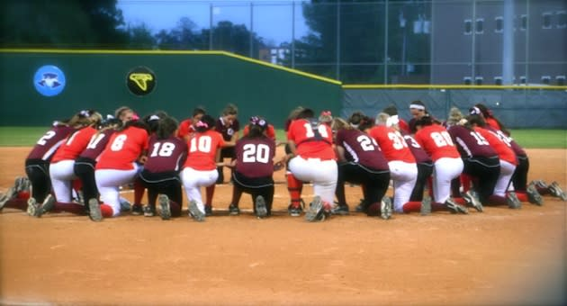 The Cinco Ranch and MacArthur softball teams join in a prayer circle — Twitter