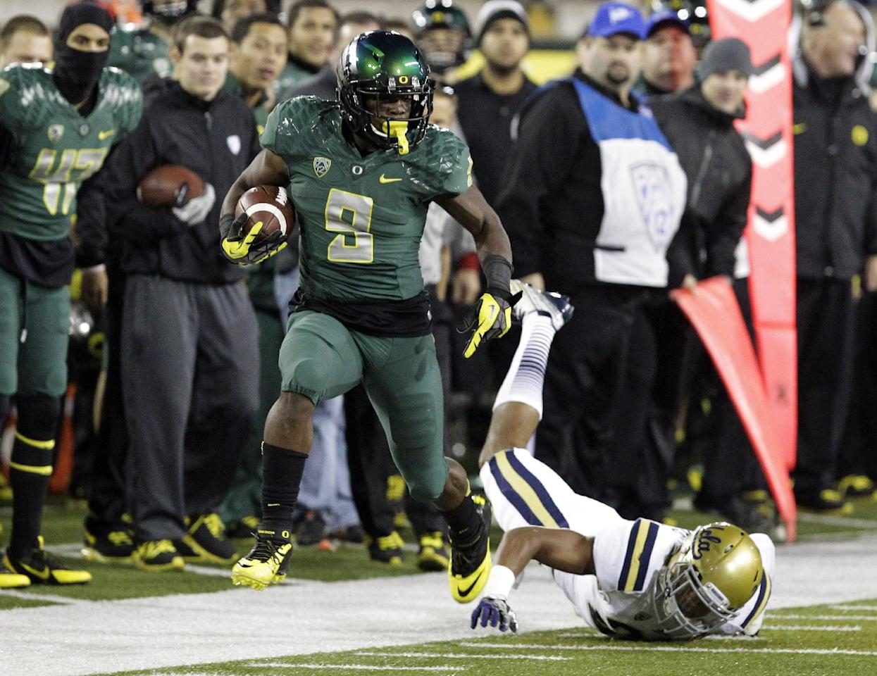 Oregon running back Byron Marshall, left, evades UCLA defender Anthony Jefferson as he heads down the sideline during the second half of an NCAA college football game in Eugene, Ore., Saturday, Oct. 26, 2013. Marshall ran for 133 yards and three touchdowns for a 42-14 victory. (AP Photo/Don Ryan)