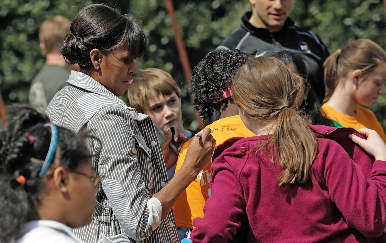 "WASHINGTON, DC - APRIL 04:  U.S. first lady Michelle Obama signs the t-shirts of schoolchildren after planting the White House Kitchen Garden on the South Lawn of the White House April 4, 2013 in Washington, DC. For the fifth time, the first lady invited students from ""schools that have made exceptional improvements to school lunches"" from Florida, Massachusetts, Tennessee and Vermont to help her plant the garden.  (Photo by Win McNamee/Getty Images)"