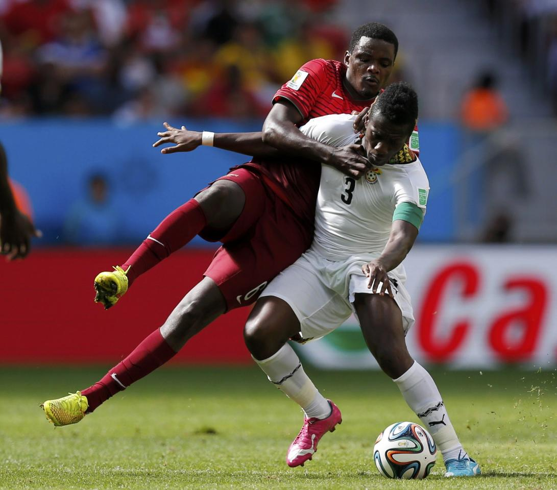 Portugal's William Carvalho (L) fights for the ball with Ghana's Asamoah Gyan during their 2014 World Cup Group G soccer match at the Brasilia national stadium in Brasilia June 26, 2014. REUTERS/Ueslei Marcelino (BRAZIL - Tags: SOCCER SPORT WORLD CUP)