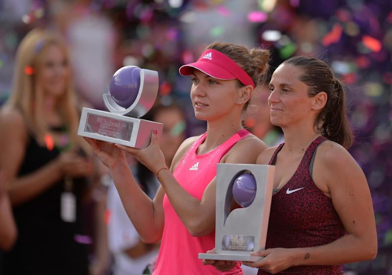Simona Halep of Romania (L) and Roberta Vinci of Italy (R) hold their trophy after the single final at the WTA Bucharest tennis tournament in Bucharest, on July 13, 2014