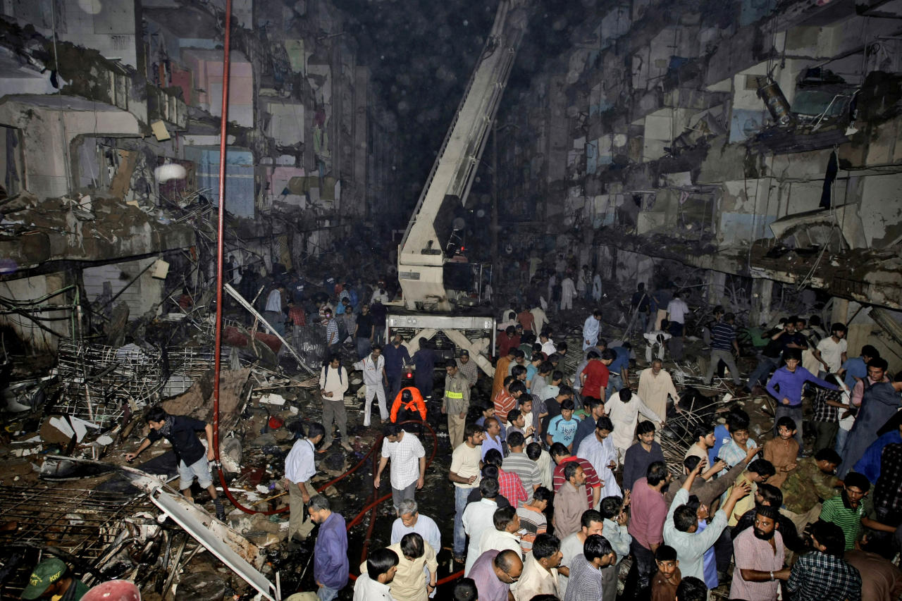 Pakistani medics and civilians gather at the site of a bomb blast in Karachi, Pakistan, Sunday, March 3, 2013. Pakistani officials say a bomb blast has killed dozens of people in a neighborhood dominated by Shiite Muslims in the southern city of Karachi. (AP Photo/Fareed Khan)