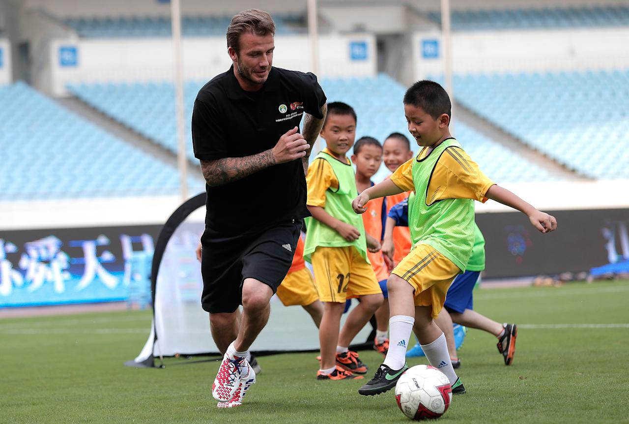 BEIJING, CHINA - JUNE 18:  David Beckham plays football with children at Nanjing Olympic Sports Center on June 18, 2013 in Nanjing, Jiangsu Province of China. David Beckham as the Chinese Super League ambassador will visit seven days in China.  (Photo by Lintao Zhang/Getty Images)