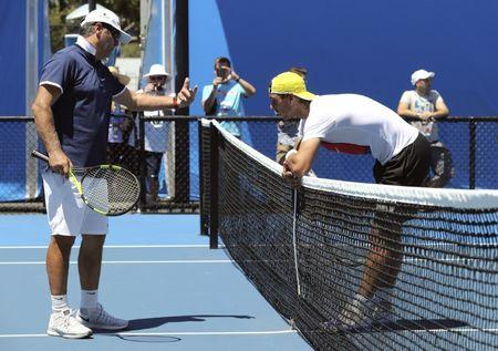 Spain's Rafael Nadal leans on the net as he talks to his coach Toni Nadal during a practice session at Melbourne Park, Australia, January 17, 2016. REUTERS/Jason O'Brien