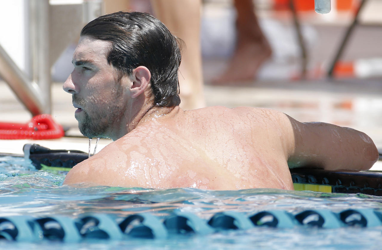 Michael Phelps looks at the scoreboard after the 100-meter butterfly during the Arena Grand Prix swim meet, Thursday, April 24, 2014, in Mesa, Ariz. It is Phelps' first competitive event after a nearly two-year retirement. (AP Photo/Matt York)