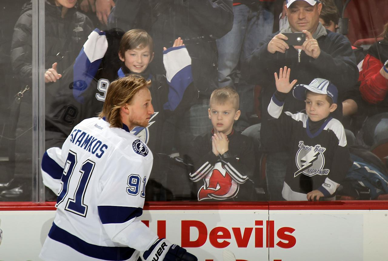 NEWARK, NJ - FEBRUARY 26: Young fans try to get the attention of Steven Stamkos #91 of the Tampa Bay Lightning during warmups prior to the game against the New Jersey Devils at the Prudential Center on February 26, 2012 in Newark, New Jersey.  (Photo by Bruce Bennett/Getty Images)