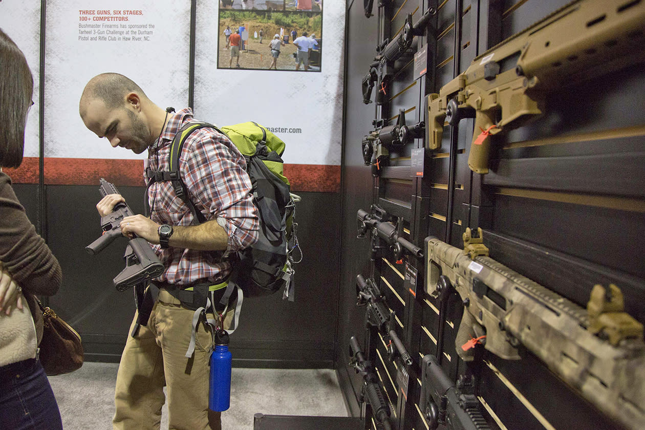 Will Michaels of Homer, La., examines a Bushmaster M4 A3 Carbine 300 AAC Blackout rifle at the Bushmaster exhibit.