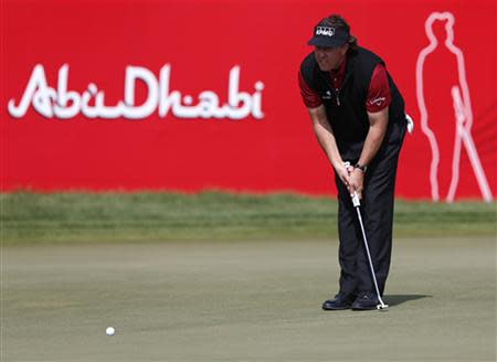 Mickelson lines the ball on the 18th green during the Abu Dhabi Golf championship