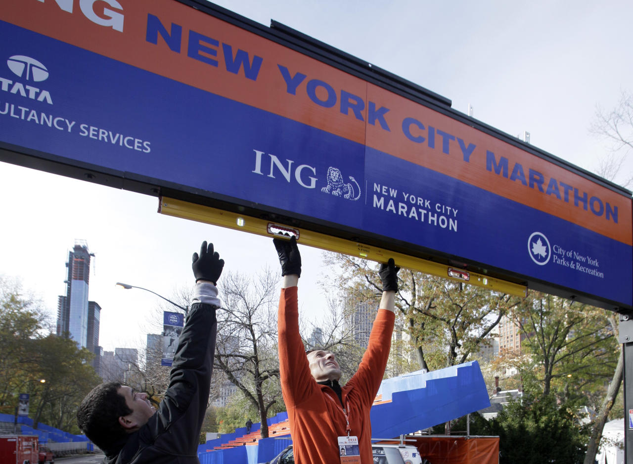 Workers assemble the finish line for the New York City Marathon in New York's Central Park, Thursday, Nov. 1, 2012. The crane atop a high rise that collapsed during superstorm Sandy is visible at background left. (AP Photo/Richard Drew)Workers assemble the finish line for the New York City Marathon in New York's Central Park, Thursday, Nov. 1, 2012. The New York City Marathon is on Sunday, with many logistical questions to be answered. (AP Photo/Richard Drew)