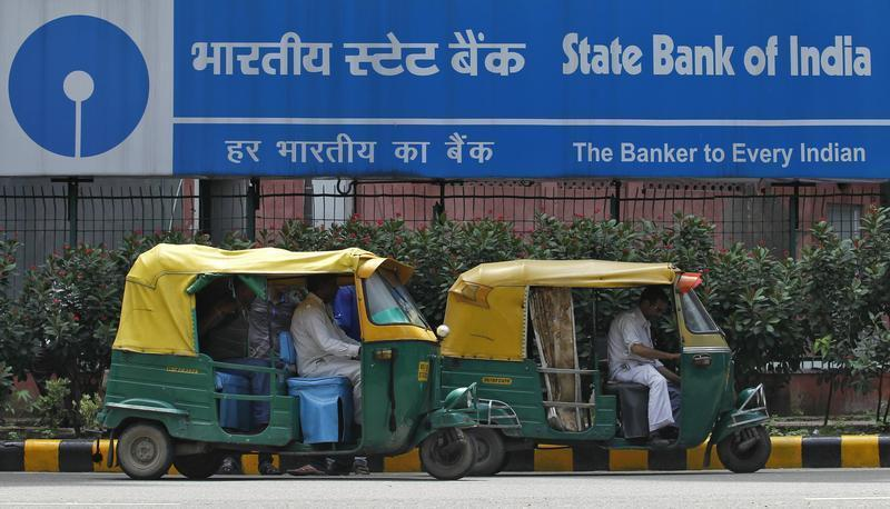 Auto rickshaws wait in front of the head office of State Bank of India in New Delhi