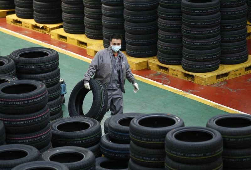 An employee carries a tyre at a tyre factory in Jiaxing, Zhejiang Province