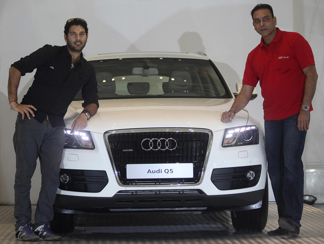 Indian cricketer Yuvraj Singh, left, poses with an Audi Q5, along with former Indian cricketer Ravi Shastri, in Mumbai, India, Thursday, April 14, 2011. Audi, the German luxury car manufacturer, presented Singh with the Audi Q5 for his performance in the ICC World Cup 2011.
