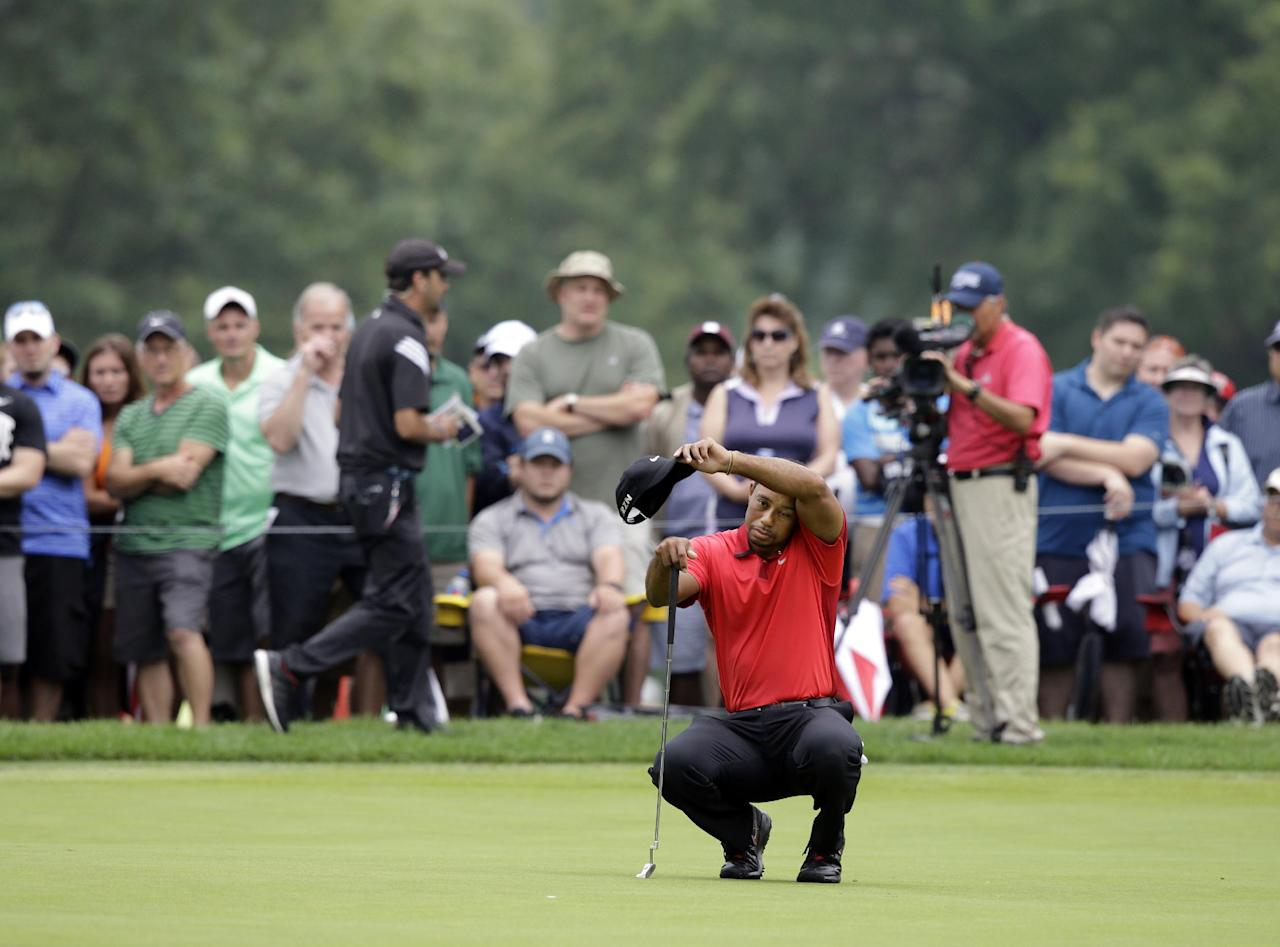 Tiger Woods looks over his putting line on the firs green during the final round of the Bridgestone Invitational golf tournament Sunday, Aug. 3, 2014, at Firestone Country Club in Akron, Ohio. (AP Photo/Mark Duncan)