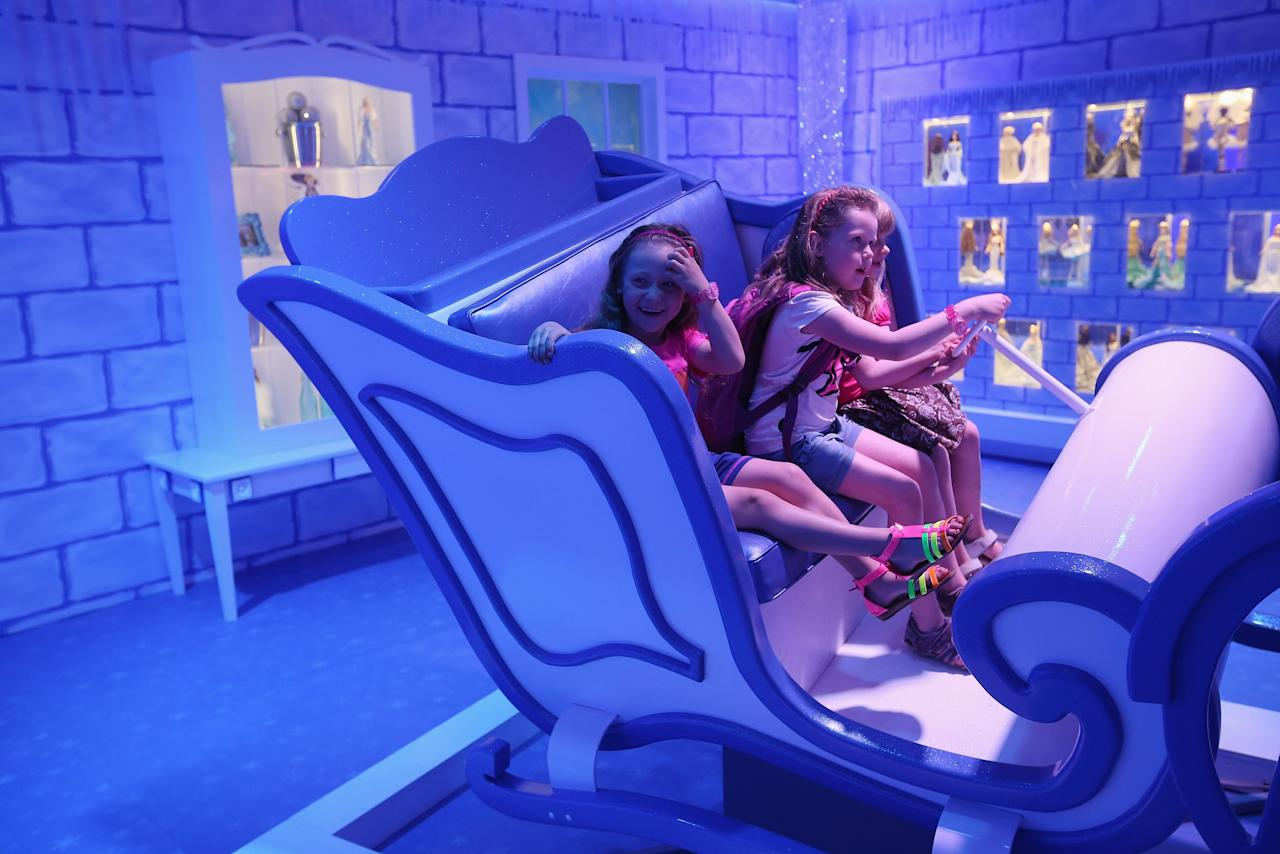 BERLIN, GERMANY - MAY 16:  Friend Luna (L), Lara (C) and Josi, all 6, play on a moving winter sled at the Barbie Dreamhouse Experience on May 16, 2013 in Berlin, Germany. The Barbie Dreamhouse is a life-sized house full of Barbie fashion, furniture and accessories and will be open to the public until August 25 before it moves on to other cities in Europe.  (Photo by Sean Gallup/Getty Images)