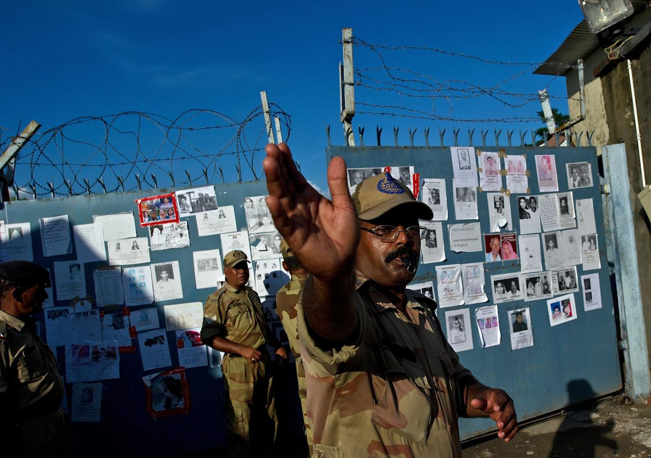 An Indian security official clears the road in front of portraits of missing pilgrims pasted on the gates of the Jolly Grant Airport in Dehradun, state capital of Uttarakhand, on June 26, 2013. Around 1,000 people have been killed in flash floods and landslides in northern India, as a top official warned June 24 that rebuilding of the devastated Himalayan region would take years.  AFP PHOTO/MANAN VATSYAYANA