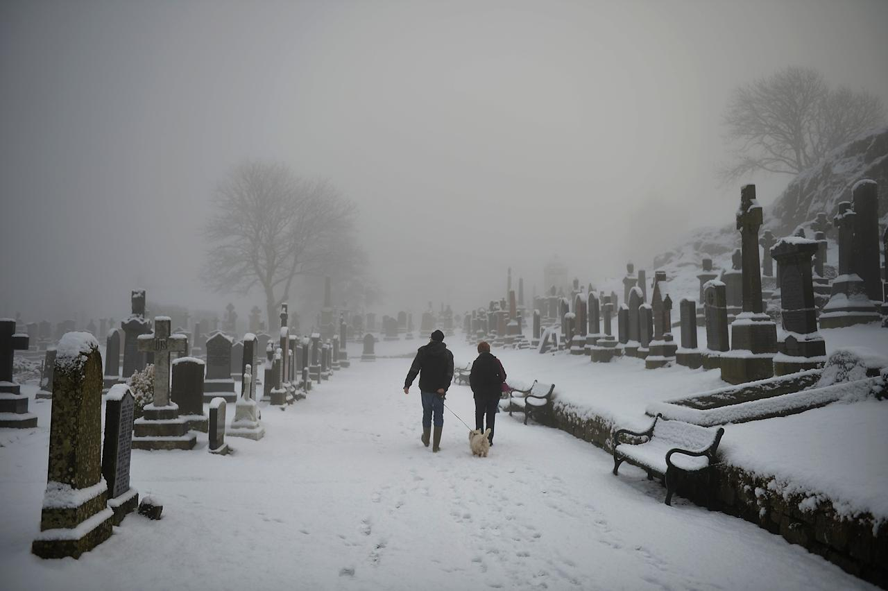STIRLING, UNITED KINGDOM - DECEMBER 03:  A man and woman walk their dog in Stirling Castle graveyard on December 3, 2012 in Stirling, Scotland.Snow and sleet has hit many parts of Scotland with heavier falls expected over higher grounds.  (Photo by Jeff J Mitchell/Getty Images)