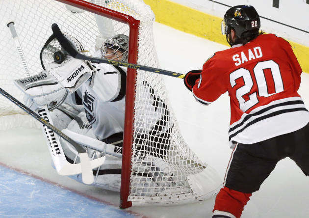 Los Angeles Kings goalie Jonathan Quick, left, saves a goal shot by Chicago Blackhawks left wing Brandon Saad (20) during the second period in Game 5 of the Western Conference finals in the NHL hockey Stanley Cup playoffs Wednesday, May 28, 2014, in Chicago. (AP Photo/Andrew A. Nelles)