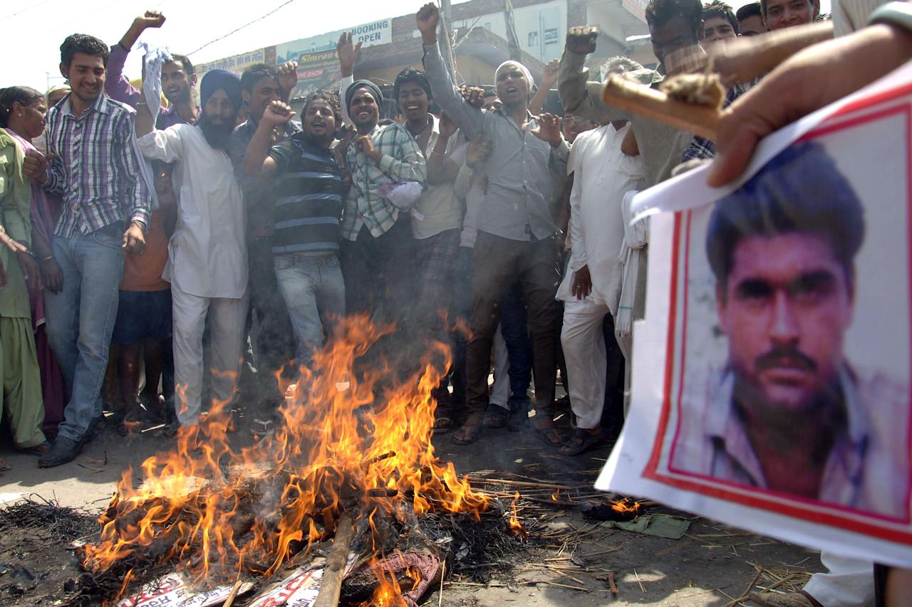 Indian villagers hold a picture of Sarabjit Singh, an Indian prisoner killed in Pakistan, as they shout-slogans while burning an effigy of  Pakistani government at Bikhiwind village, some 45 km from Amritsar on May 2, 2013. An Indian man on death row in Pakistan for spying died nearly a week after he was attacked by fellow prisoners, who were swiftly charged with murder as New Delhi demanded justice. Sarabjit Singh, who was sentenced 16 years ago over deadly bombings, died in the early hours as a result of the savage assault in Lahore's Kot Lakhpat jail, a senior doctor at Jinnah hospital in the eastern city told AFP.  AFP PHOTO / NARINDER NANU        (Photo credit should read NARINDER NANU/AFP/Getty Images)