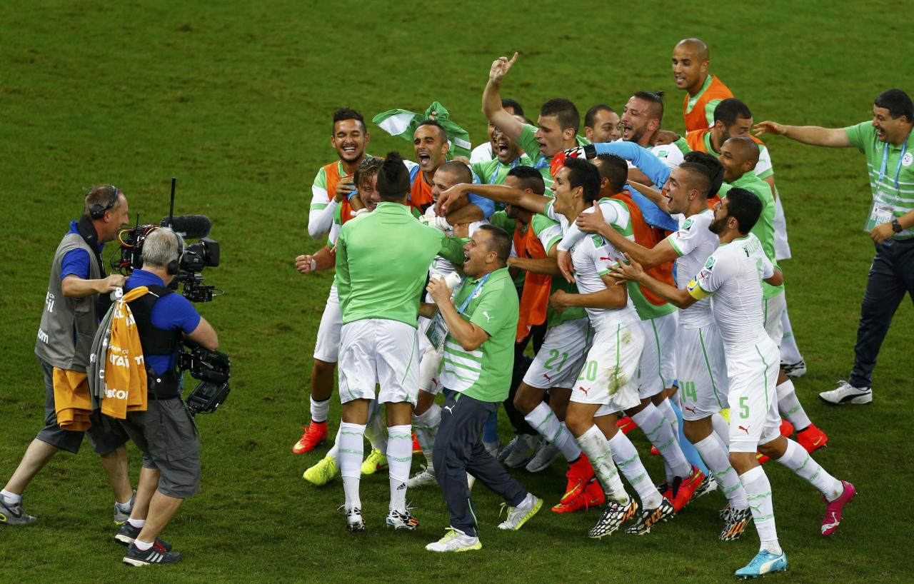 Algeria's national soccer team celebrates in front of the camera after their 2014 World Cup Group H soccer match against Russia at the Baixada arena in Curitiba June 26, 2014. 