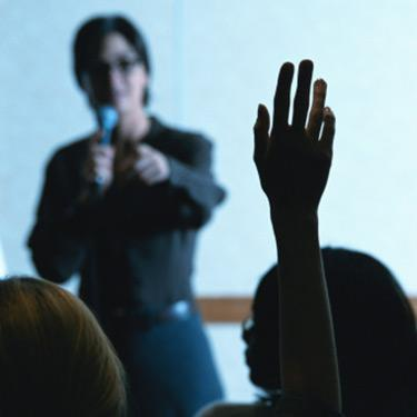 Woman-holding-mic-giving-presentation_web