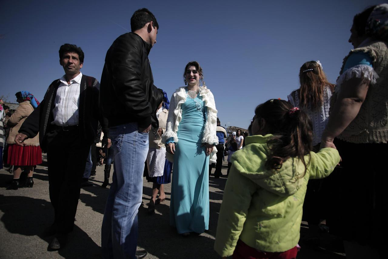 """This Saturday, March 23, 2013 photo shows Roma bride-to-be from the Kalaidzhi community during so called """"Roma bridal market"""". The Kalaidzhi, who represent only a small portion of the estimated 700,000 Roma in Bulgaria, are almost all devout Orthodox Christians who keep teenage boys and girls separate. Parents sometimes remove girls from school at 15 or even earlier to keep them from mixing with boys. The isolation is broken only by Internet chats and the twice-a-year bridal fairs. (AP Photo/Valentina Petrova)"""
