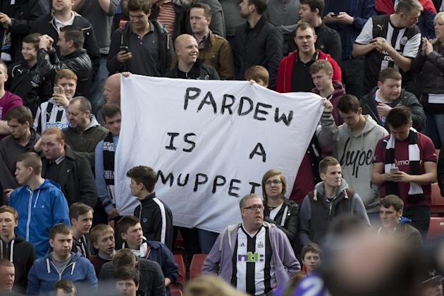 Newcastle United supporters hold up a banner critical of their manager Alan Pardew before their team's English Premier League soccer match against Stoke at the Britannia Stadium, Stoke, England, Saturday April 12, 2014. (AP Photo/Jon Super)
