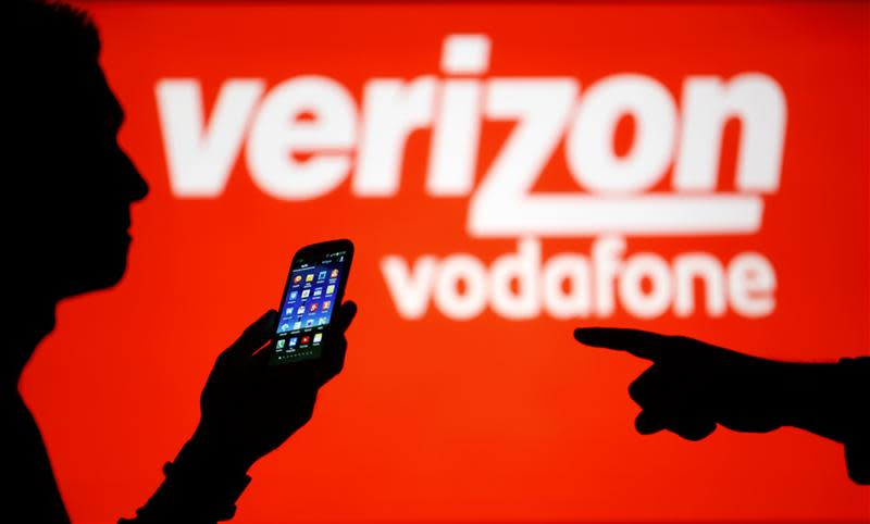 A man is silhouetted against a video screen with Vodafone and Verizon texts as he poses with a Samsung Galaxy S3 in this photo illustration taken in the central Bosnian town of Zenica