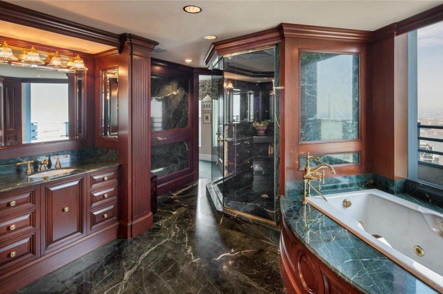 The master bath has hunter green marble, mahogany finishes, and bronze fixtures.