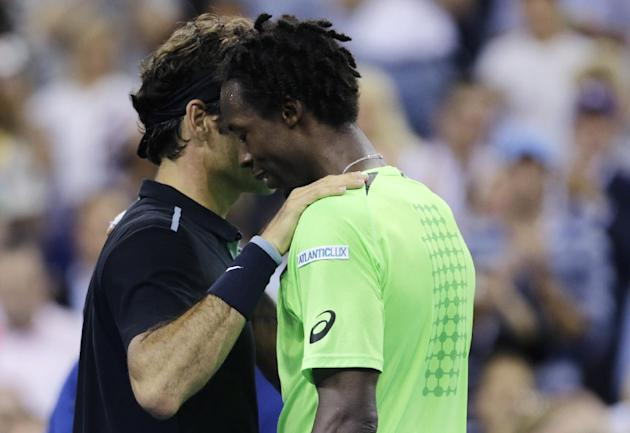 Roger Federer, of Switzerland, gives Gael Monfils, of France, a pat on the shoulder his victory Thuesday night. (AP Photo/Charles Krupa)