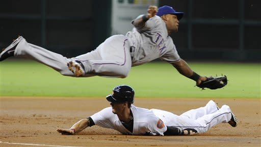 Houston Astros' Jordan Schafer slides beneath Texas Rangers third baseman Texas Rangers' Adrian Beltre to steal third base in the first inning of an interleague baseball game, Friday, May 18, 2012, in Houston. (AP Photo/Pat Sullivan)