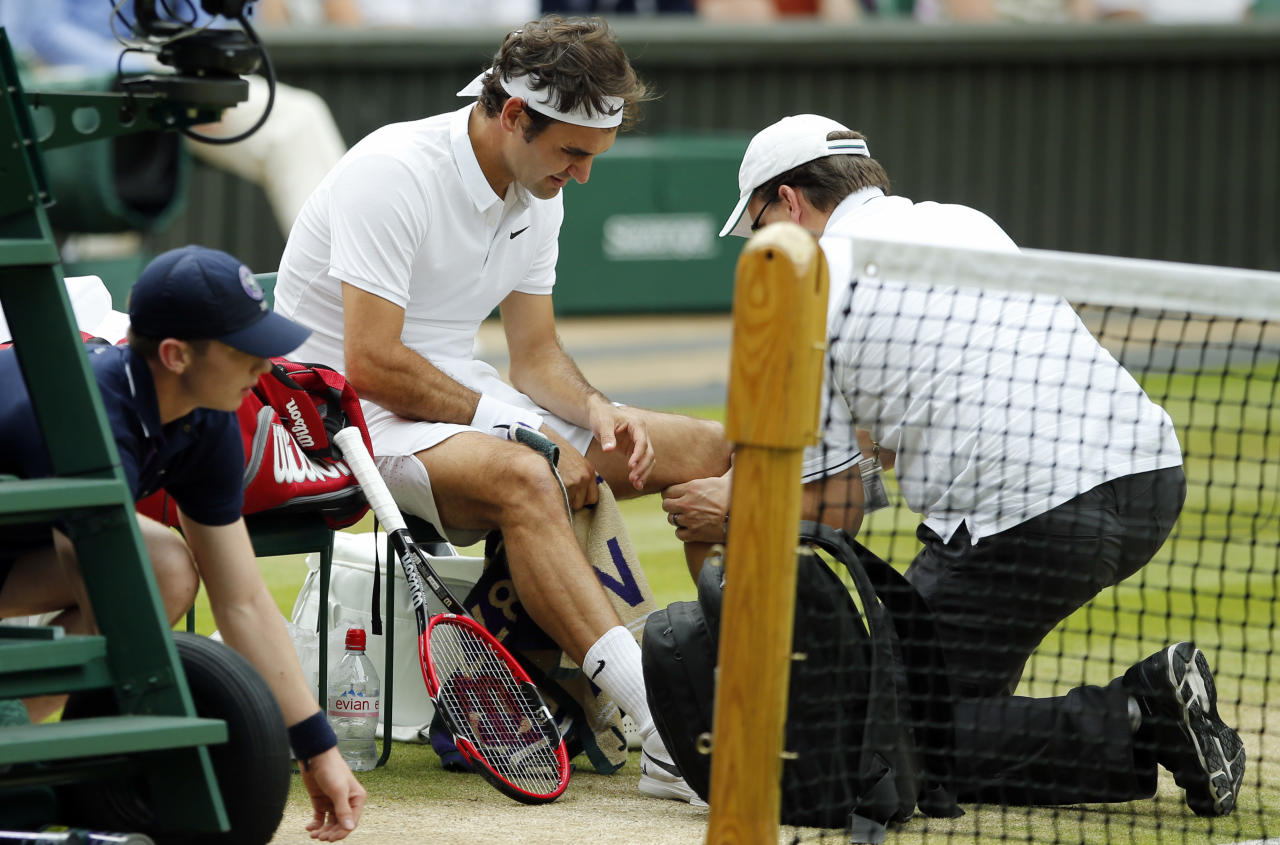 FILE - In this July 8, 2016, file photo, Roger Federer of Switzerland receives medical attention during his men's semifinal singles match against Milos Raonic of Canada at the Wimbledon Tennis Championships in London. Federer says he contemplated scenarios in which he would play in the Olympics and skip the U.S. Open, and vice versa. In the end, his balky left knee wouldn't allow him to do either. (AP Photo/Alastair Grant, File)