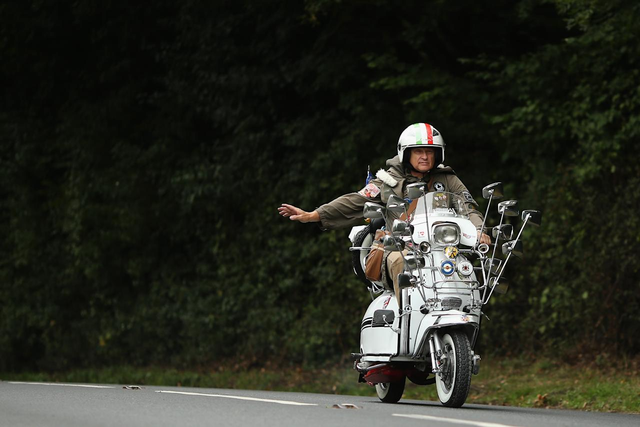 RYDE, ENGLAND - AUGUST 24: A scooter rider makes his way along a country lane during the the Isle of Wight International Scooter Rally on August 24, 2013 in Ryde, England. The annual event, which is organized by the British Scooter Rally Association and The VFM Scooter Collective, attracts around 6000 riders each year and has been running since 1980. The scooter in 1960's Britain was a fashion statement and the often heavily customized bikes, usually an Italian Vespa or Lambretta, became synonymous with the Mod scene. They provided an inexpensive mode of transport and escapism to an upwardly mobile youth at a time when public transportation stopped early. The Vespa was depicted on the cover of 'The Who's Quadrophenia album in 1973. (Photo by Dan Kitwood/Getty Images)