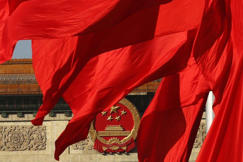 The Great Hall of the People, where the Chinese Communist Party plenum is being held, is seen behinds red flags in Tiananmen square in Beijing