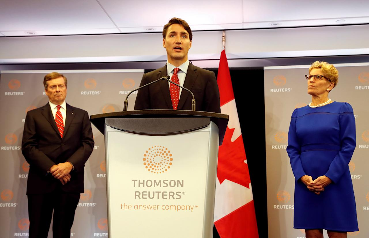 Canada's Prime Minister Justin Trudeau speaks beside Ontario Premier Kathleen Wynne (R) and Toronto Mayor John Tory (L) during a visit to the Thomson Reuters Executive office in Toronto, Ontario, Canada October 7, 2016. REUTERS/Mark Blinch