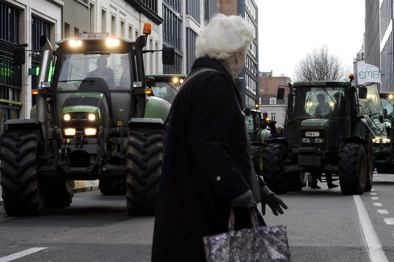 An elderly woman crosses a street in front of the tractors of European milk farmers in the European quarter of Brussels.