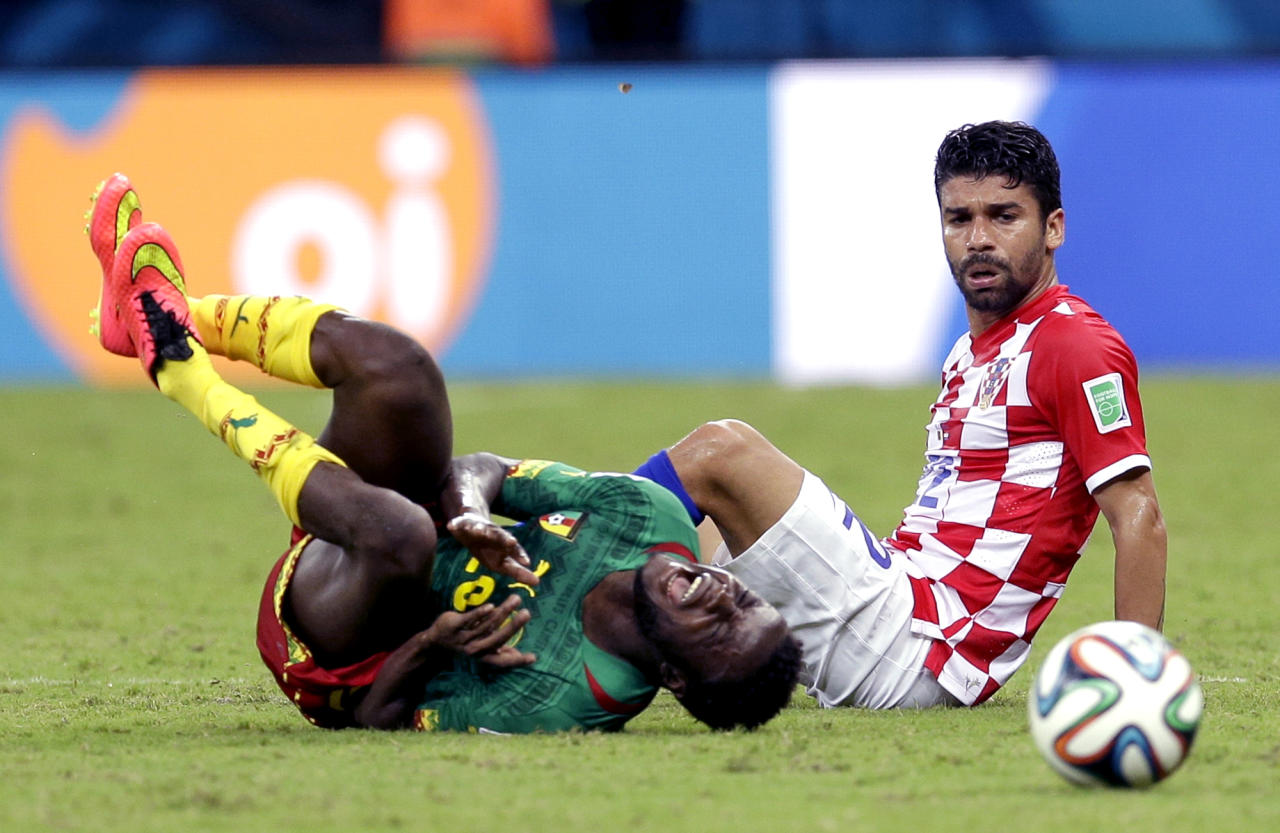 Cameroon's Edgar Salli, left, shouts out after being fouled by Croatia's Eduardo during the group A World Cup soccer match between Cameroon and Croatia at the Arena da Amazonia in Manaus, Brazil, Wednesday, June 18, 2014. (AP Photo/Themba Hadebe)