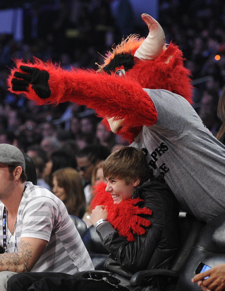 The Chicago Bulls mascot jokes around with Justin Bieber during the first half of the NBA basketball All-Star Game on Sunday, Feb. 20, 2011, in Los Angeles.