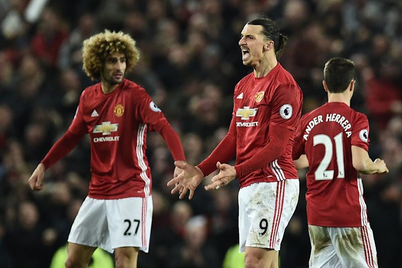 Manchester United's striker Zlatan Ibrahimovic (C) celebrates scoring his team's first goal with midfielder Marouane Fellaini (L) during the English Premier League football match against Liverpool January 15, 2017