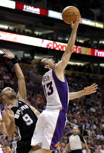 Phoenix Suns' Steve Nash (13) shoots a reverse layup, and misses, in front of San Antonio Spurs' Tony Parker (9), of France, during the second quarter of an NBA basketball game Tuesday, March 27, 2012, in Phoenix. (AP Photo/Ross D. Franklin)