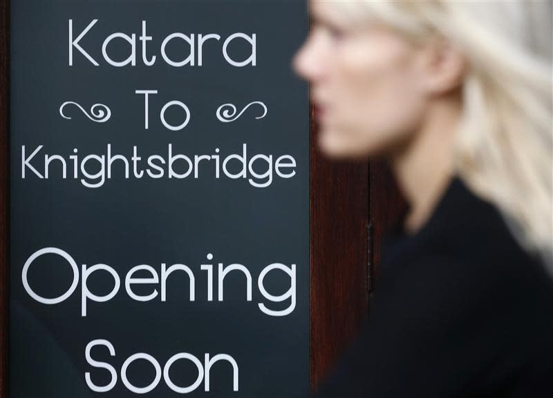 A woman passes a new coffee shop to be opened in London